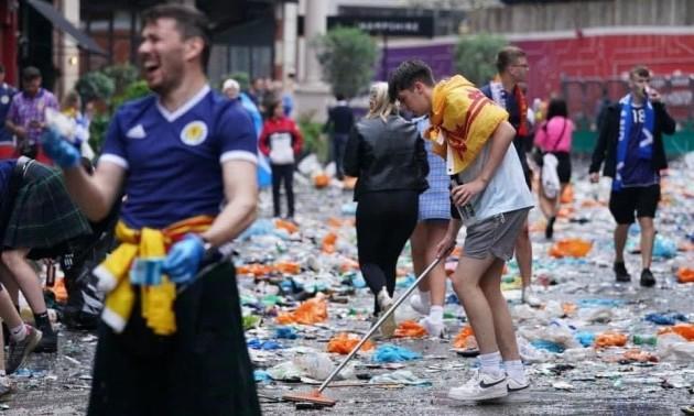 Фото дня. Шотландські фани прибирають вулиці Лондона після масових безладів